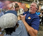 A supporter of Republican presidential hopeful Donald Trump scuffles with a protestor during a rally in Richmond, Va., Wednesday, Oct. 14, 2015. (AP Photo/Steve Helber)